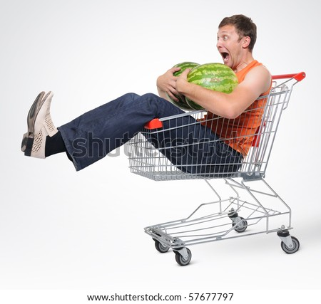Crazy man in shopping-cart with two watermelon - stock photo
