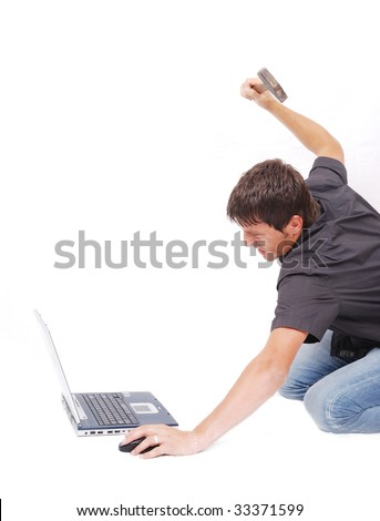 Crazy man is destroying a laptop with hammer - stock photo