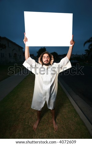Crazy man with blank billboard sign on a street at night.