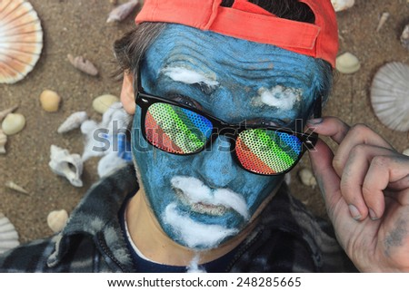 crazy man with blue face wearing rainbow glasses - stock photo