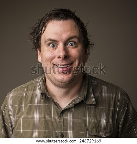 Crazy man with messed up hair and wild eyes staring at the camera - stock photo