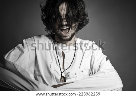Crazy man with straitjacket screaming trying to break free against gray background with copyspace - stock photo
