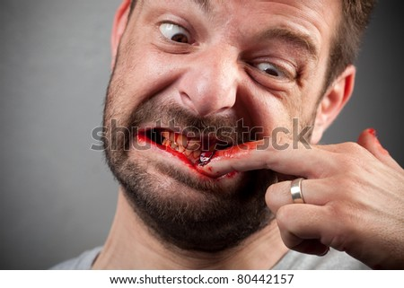 Crazy nailbiter. A man biting of his nails, his fingers are covered in blood. Bloody series. - stock photo