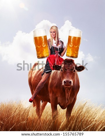 crazy oktoberfest or tiroler creation with a very beautiful woman is sitting on a cow and serving beer - stock photo
