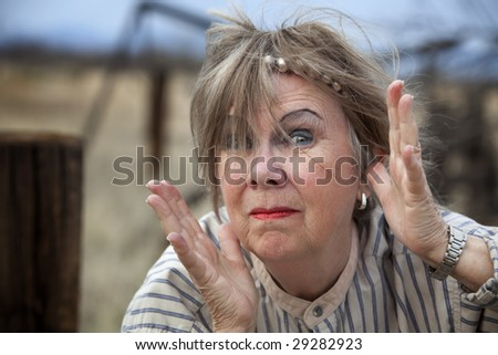 Crazy old woman outdoors with wild makeup - stock photo
