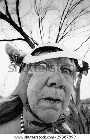 Crazy old woman wearing a Viking helmet - stock photo