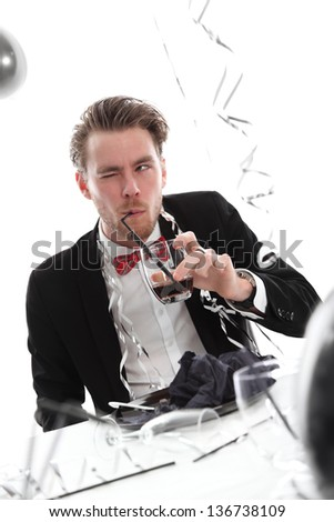 Crazy party guy with glass. Wearing a black suit and bowtie. White background. - stock photo