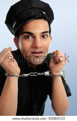Crazy policeman with hands in handcuffs arrest. - stock photo