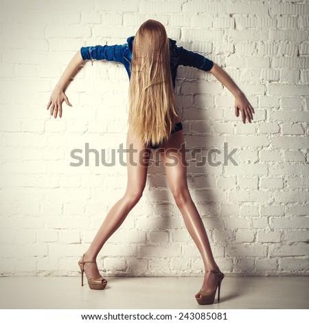 crazy posing young long legs model. fashion photo. long blonde hair. - stock photo