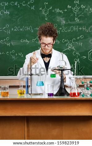 Crazy professor works in his laboratory - stock photo