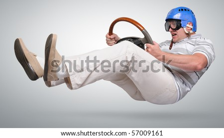 Crazy racer in goggles with wheel - stock photo
