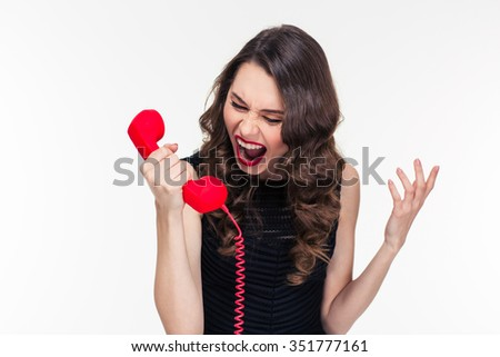 Crazy raged retro styled curly young female shouting in red telephone receiver over white background - stock photo