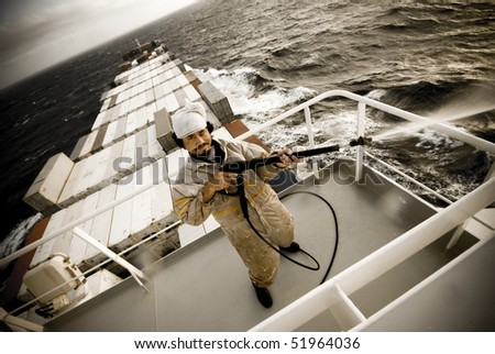 crazy seaman at work onboard huge ship - stock photo