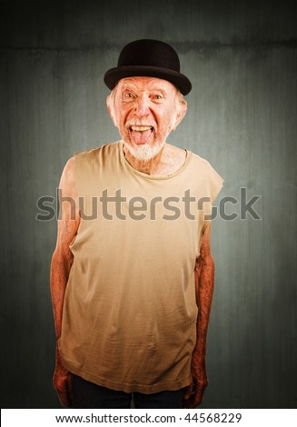 Crazy senior man in bowler hat sticking out his tongue - stock photo