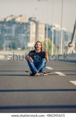 Crazy skateboarder sitting on his skateboard at the middle of a highway traffic bridge