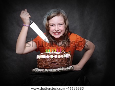Crazy smiling girl with bread-knife and her birthday chocolate cake. Studio shot. - stock photo