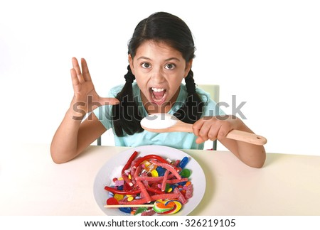 crazy spastic hispanic female child eating dish full of candy and gummies holding sugar spoon in wrong dangerous diet and sweet nutrition abuse and excess isolated on white background - stock photo