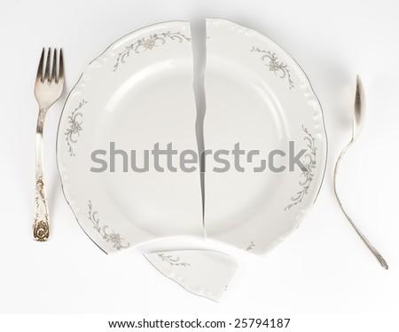Crazy table arrangement - split plate and bent silverware - stock photo