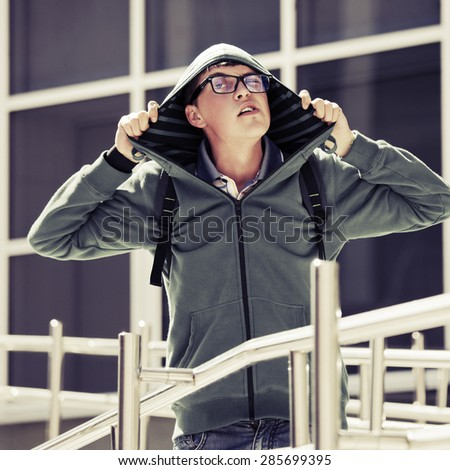 Crazy teen boy with backpack against a school building