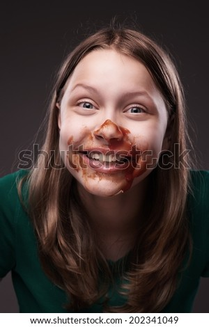 Crazy teen grl sitting and laughing with ketchup or blood on her face - stock photo