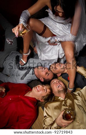 Crazy wedding party in night club. bride making a drunkard of friends of groom - stock photo
