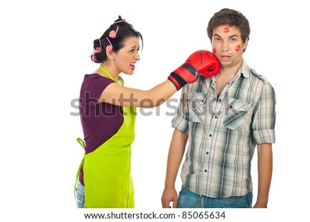 Crazy wife having conflict with surprised unfaithful husband and kick his face with boxing glove against white background - stock photo