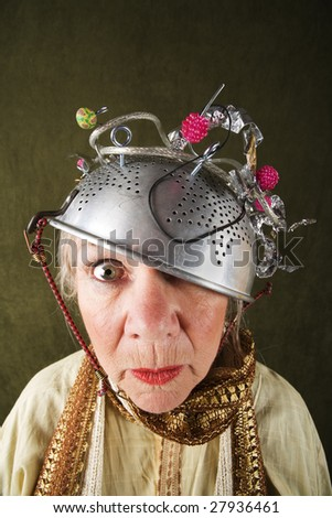 Crazy woman wearing a metal colander for a helmet - stock photo