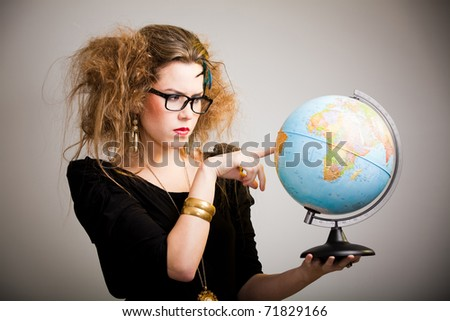 Crazy woman with messy hairdo holding a globe - stock photo