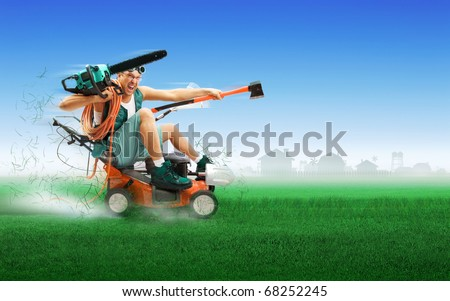 Crazy workman covered with instruments driving lawn mower over green grass - stock photo