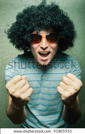 crazy young guy in afro curly wig with eyeglasses - stock photo
