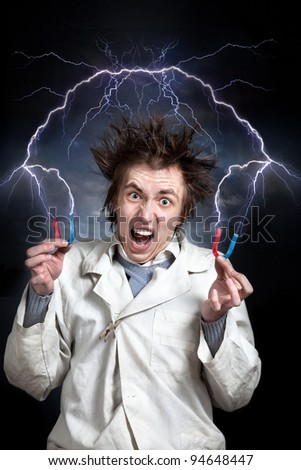 Crazy young professor with magnets in white coat. Thunder strikes from magnets around him - stock photo