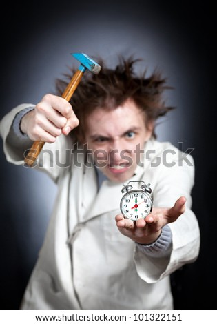 Crazy young student in white coat trying to break his alarm clock with his hammer which shows six am