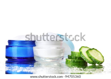 cream and fresh sliced cucumber on table isolated on white - stock photo