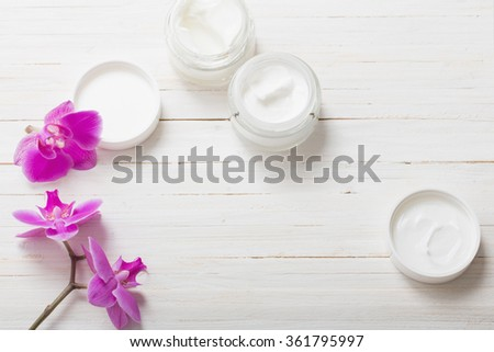 cream and pink orchid flowers on white wooden background