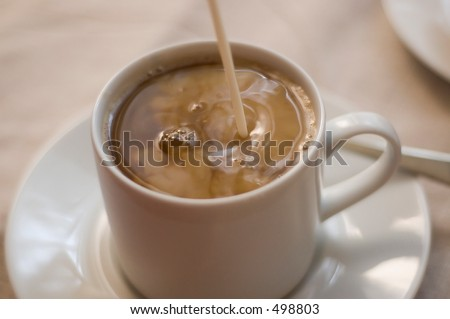 cream being poured into coffee - stock photo