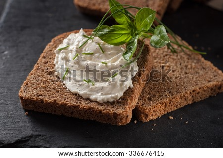 Cream cheese with herbs and seasoning on a slice of fresh rye bread - stock photo