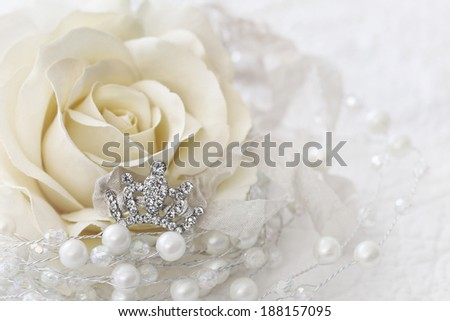 Cream color rose with small jeweled crown - stock photo