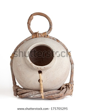 Cream colored birdhouse jug partially wrapped in a twig holder held together with leather straps. white background, front view.