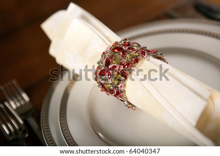 Cream colored festive napkin with ornate fancy napkin ring on a holiday table - stock photo