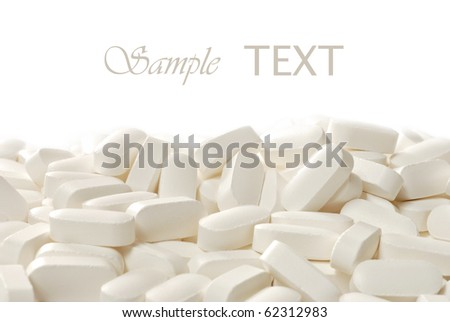 Cream colored nutritional supplements (calcium, magnesium, vitamin d) on white background with copy space.  Macro with shallow dof. - stock photo