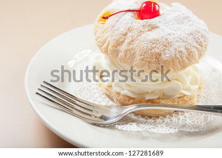 Cream filled puff pastry with cherry on top. - stock photo