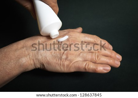 Cream for hands, over a dark background. Cosmetic, medicine concept.