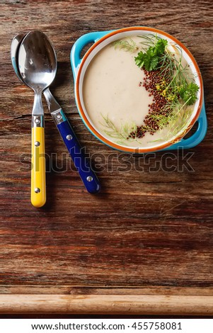 Cream homemade mushroom soup in a blue plate with parsley colored spoons.  - stock photo