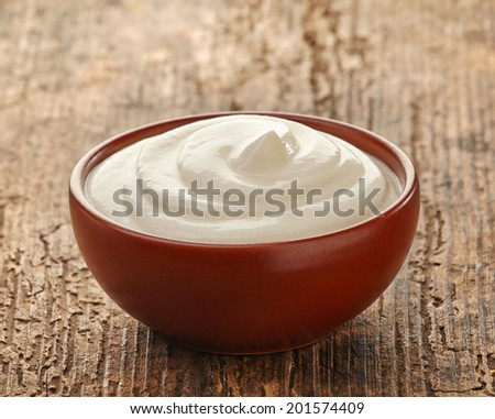 cream in a brown ceramic bowl on a wooden table - stock photo