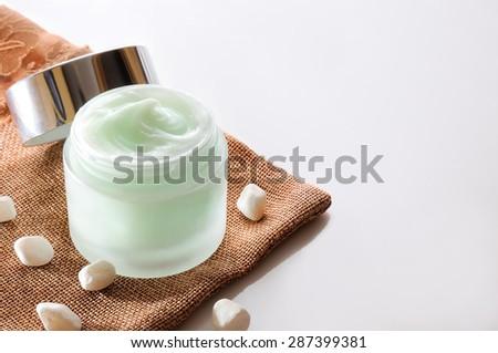 Cream jar open on burlap top isolated - stock photo