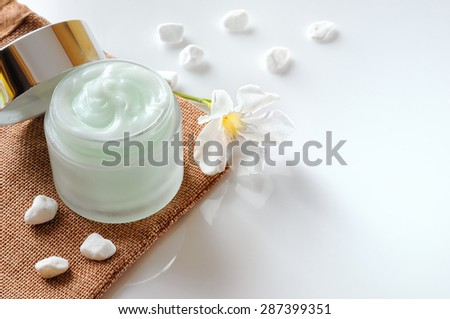 Cream jar open on burlap with stones and flower top isolated on white table - stock photo