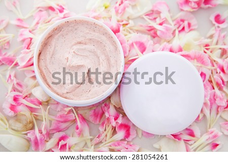 cream jar with flower petal - stock photo