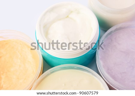 Cream jars on grey background. - stock photo