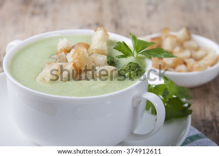 Cream of broccoli with croutons and parsley in a white cup on a wooden table.