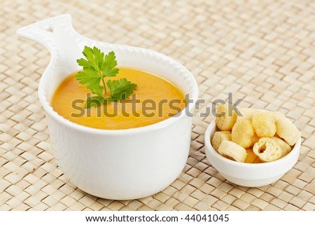 Cream of carrot soup with parsley and bread croutons. Focus at front and shallow depth of field
